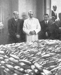 Pius XII looks at the food that the Vatican prepared for war prisoners and refugees